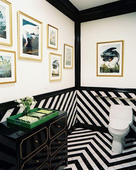 Banheiro preto e branco com quadros relacionados a natureza.