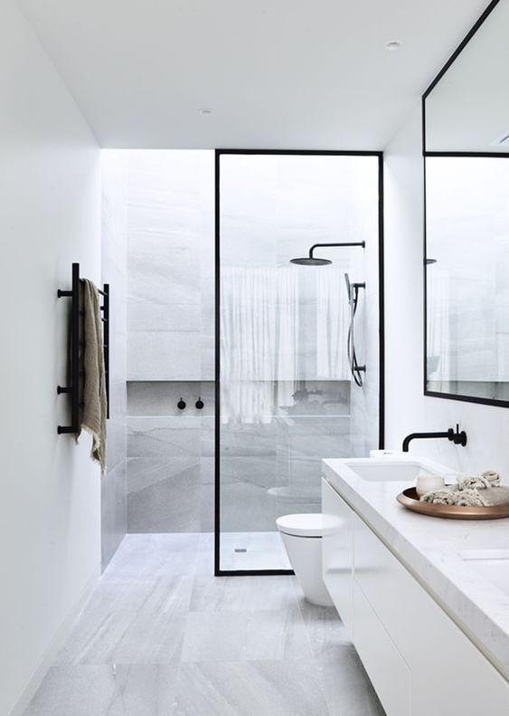 Banheiro minimalista preto e branco com artigo decorativo na pia.