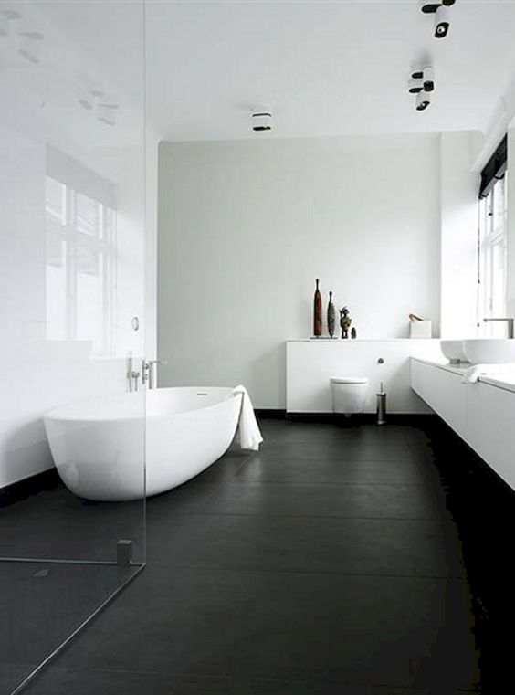 Banheiro grande com banheira, duas pias e chão preto.
