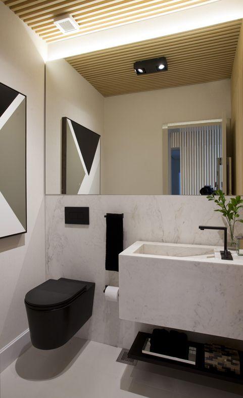 Banheiro preto e branco decorado com quadro e vaso de planta.