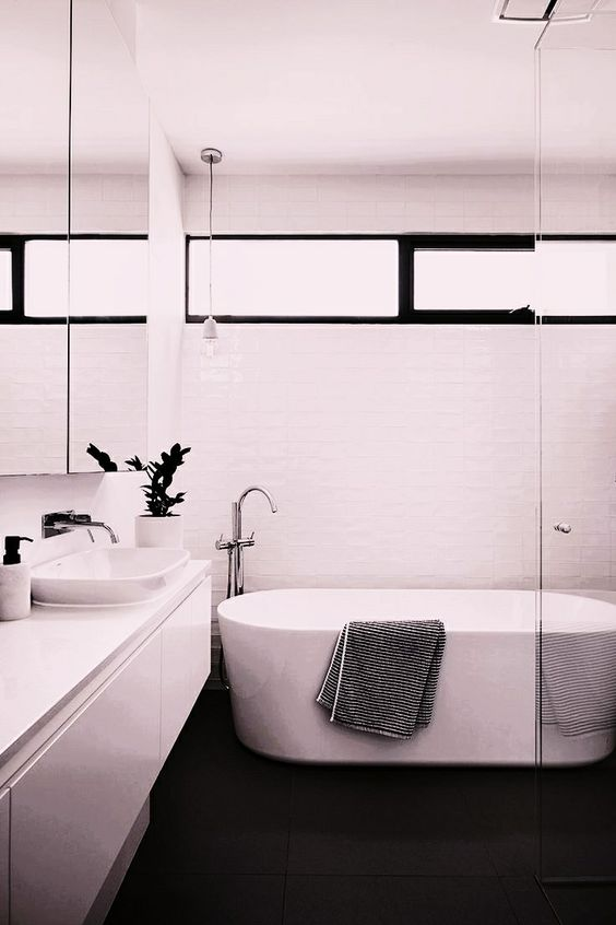 Banheiro com pia, banheira e paredes brancas e chão preto.