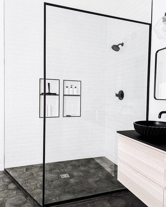 Banheiro branco com detalhes pretos e chão acimentado.