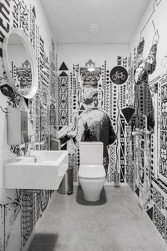 Banheiro com todas as paredes brancas com diversos desenhos pretos.