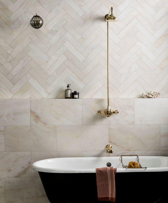 Banheiro decorado com banheira preta e branca e chuveiro dourado.