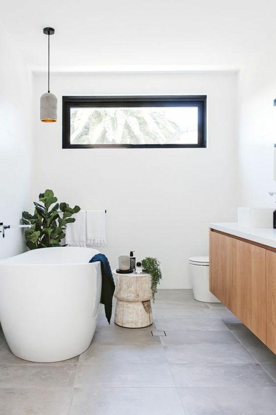 Banheiro branco com detalhe preto na janela e plantas decorativas.