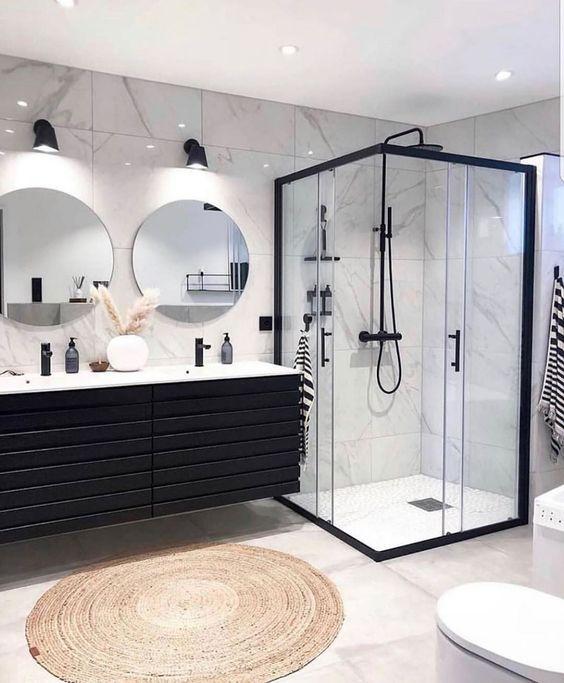 Banheiro preto e branco decorado com tapete redondo.