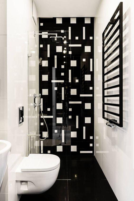 Banheiro com parede preta com com desenhos geométricos brancos.