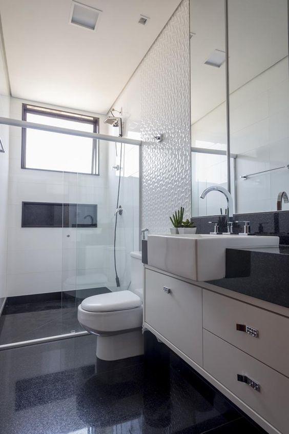 Banheiro com chão preto e parede com textura branca.