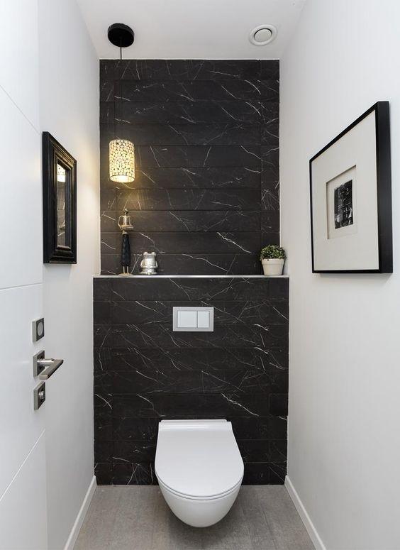 Banheiro decorado com quadros, plantas, esculturas e parede preta.