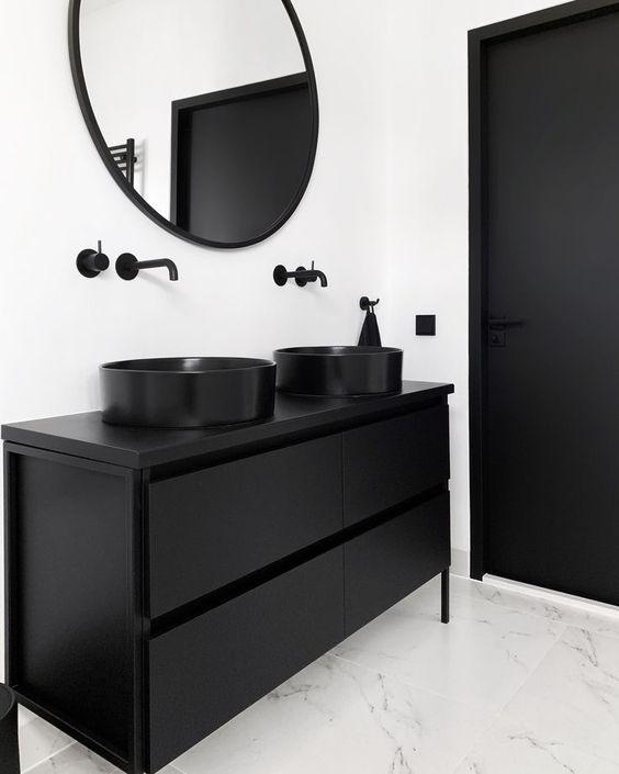 Banheiro minimalista com revestimento branco e torneira, pia, armário e porta pretas.