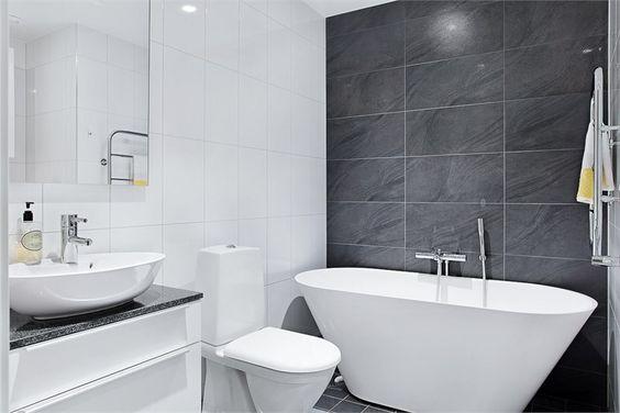 Banheiro com balcão da pia e parede central pretos.