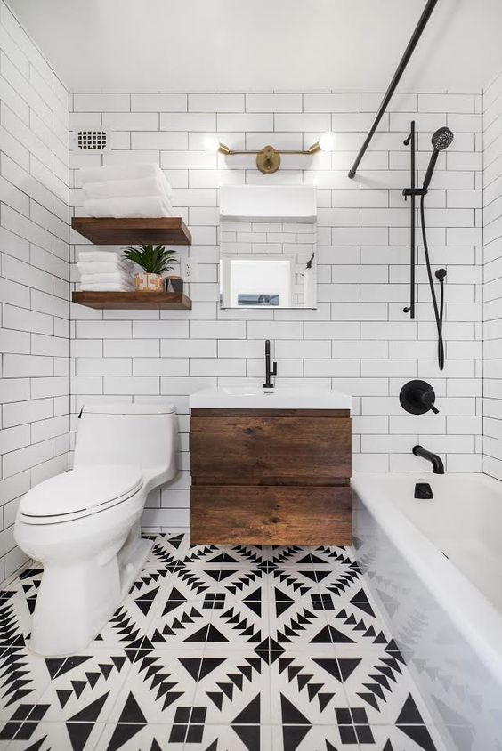 Banheiro branco com detalhes pretos no chuveiro, torneira e desenhos no chão.