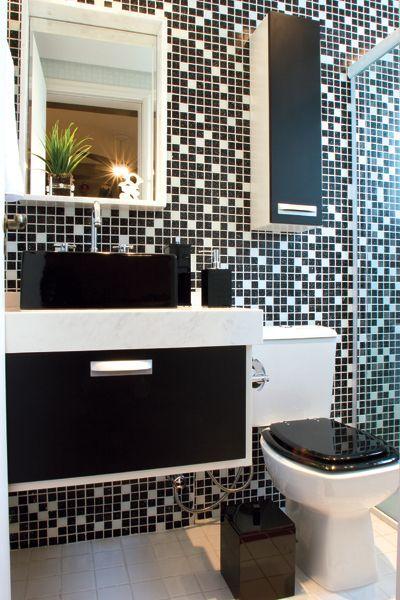 Banheiro preto e branco com parede revestida de pastilhas.