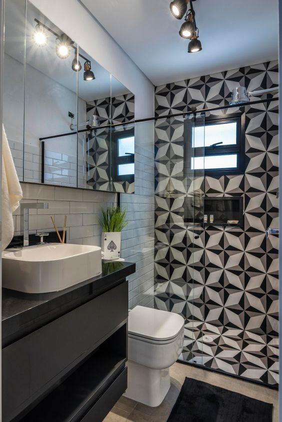 Banheiro preto e branco com iluminação direcionada e parede principal combinando com o chão.