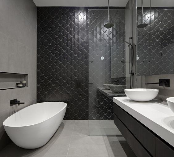 Banheiro minimalista com parede central com desenho de escamas pretas.