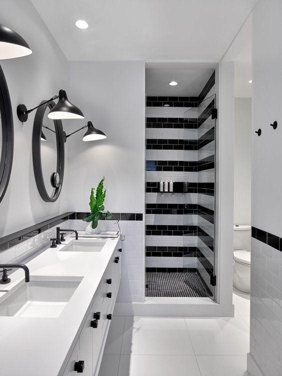 Banheiro preto e branco com área do box listrada.