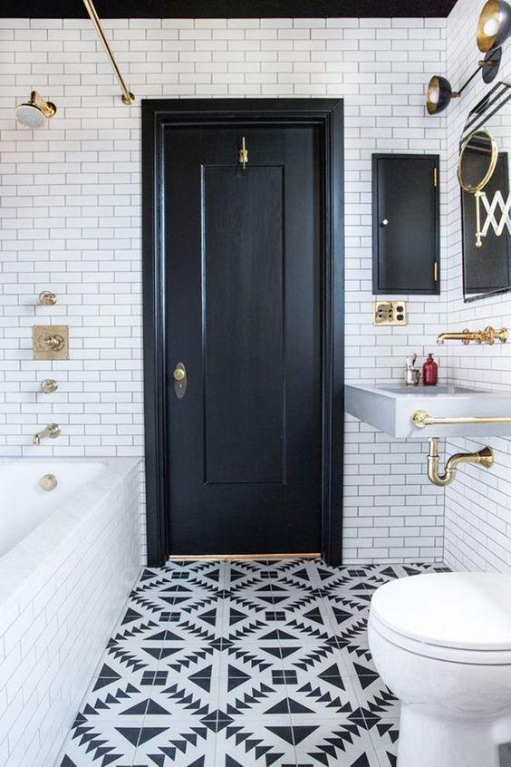 Banheiro com paredes brancas, porta preta e chão desenhado com as duas cores.
