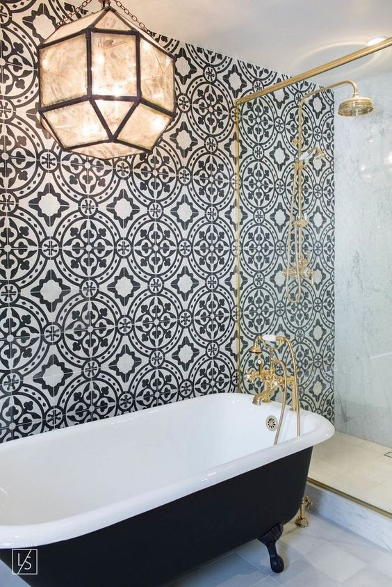 Banheiro retrô com parede preta e branca, banheira da mesma cor e torneira com chuveiro dourados.