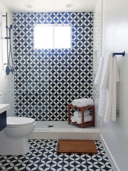 Banheiro com parede e chão preto e branco com o mesmo revestimento desenhado.