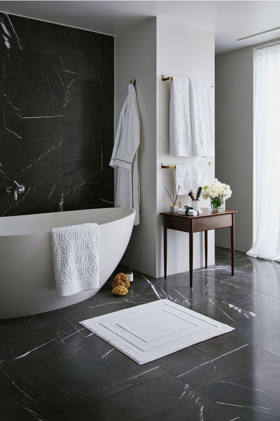 Banheiro preto e branco decorado com toalhas e tapete.