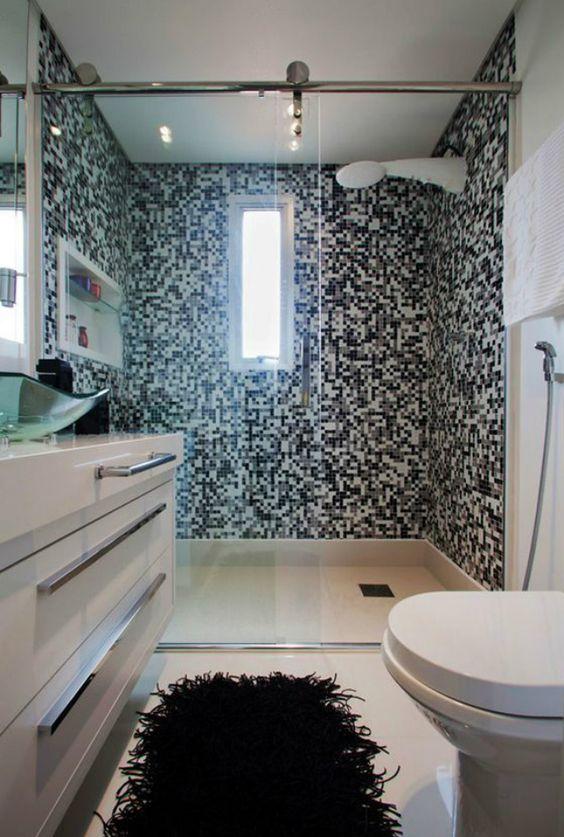 Banheiro com as paredes do box em pastilhas preta, branca e cinza.