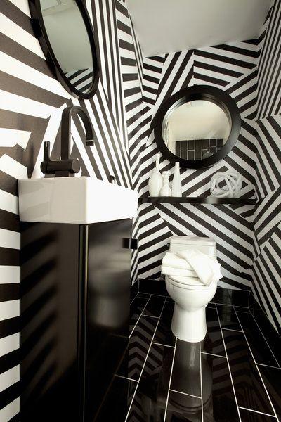Lavabo preto e branco com dois espelhos redondos.