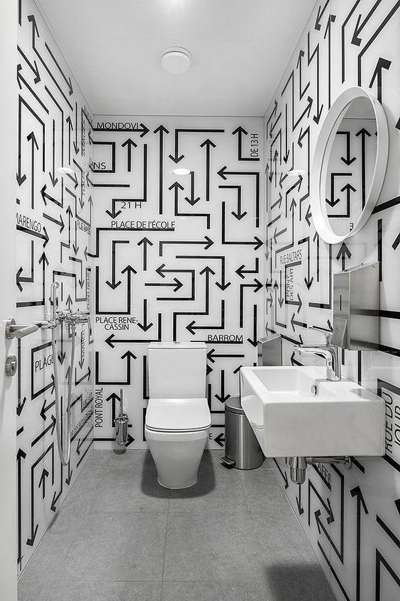 Banheiro com desenhos de setas e nomes de cômodos nas paredes.