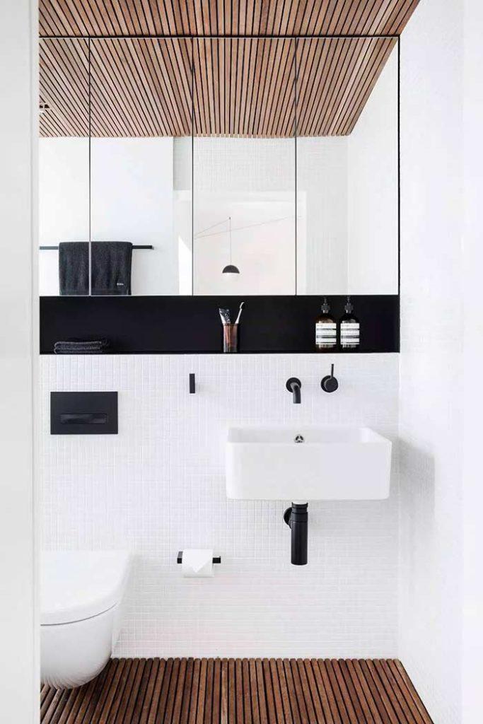 Banheiro branco com piso e teto em madeira