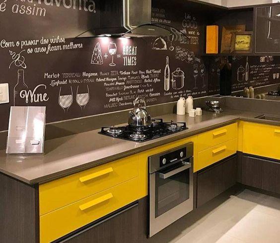 cozinha moderna amarela e cinza com parede lousa preta