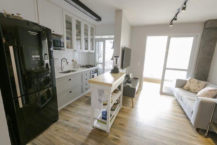 Decoração com armários brancos e geladeira preta.