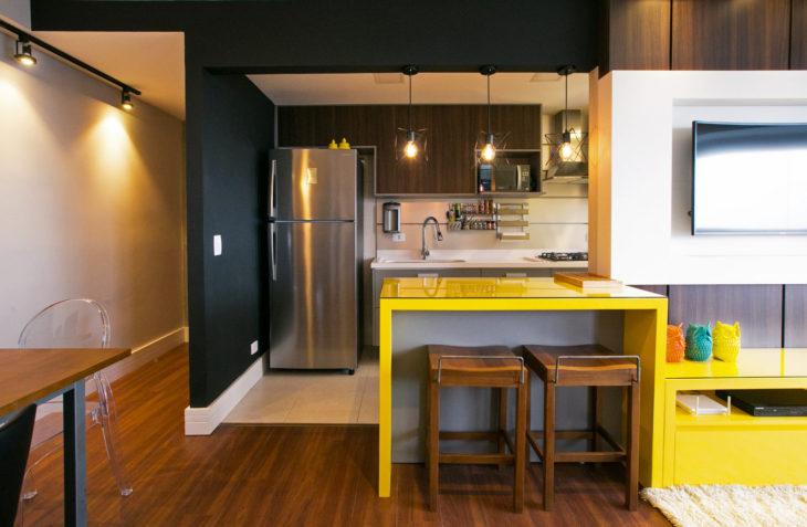Decoração moderna com geladeira de aço inox e bancada amarela.