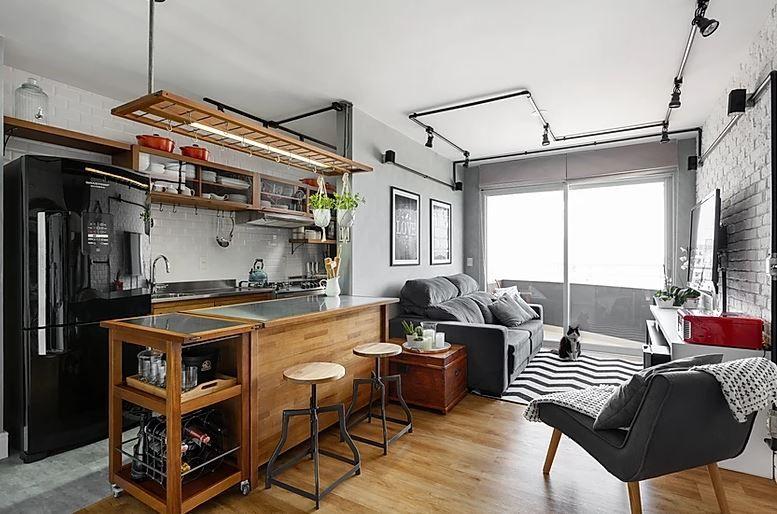 Decoração rústica com geladeira preta, bancada de madeira e minibar.