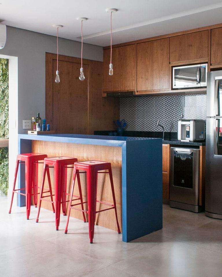Decoração com armário azul e banquetas vermelhas.