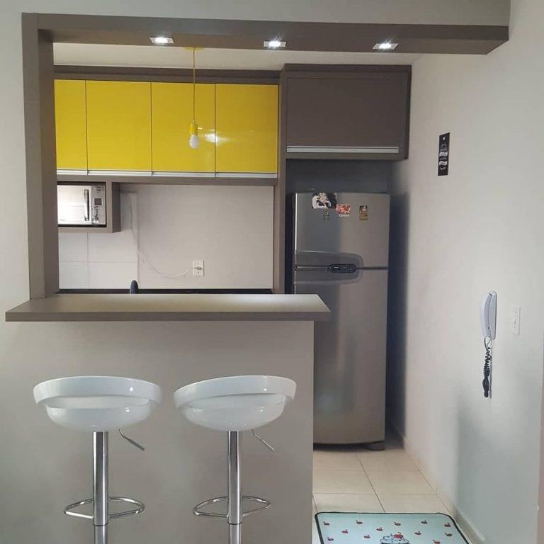 Decoração simples com armário amarelo e banquetas brancas.