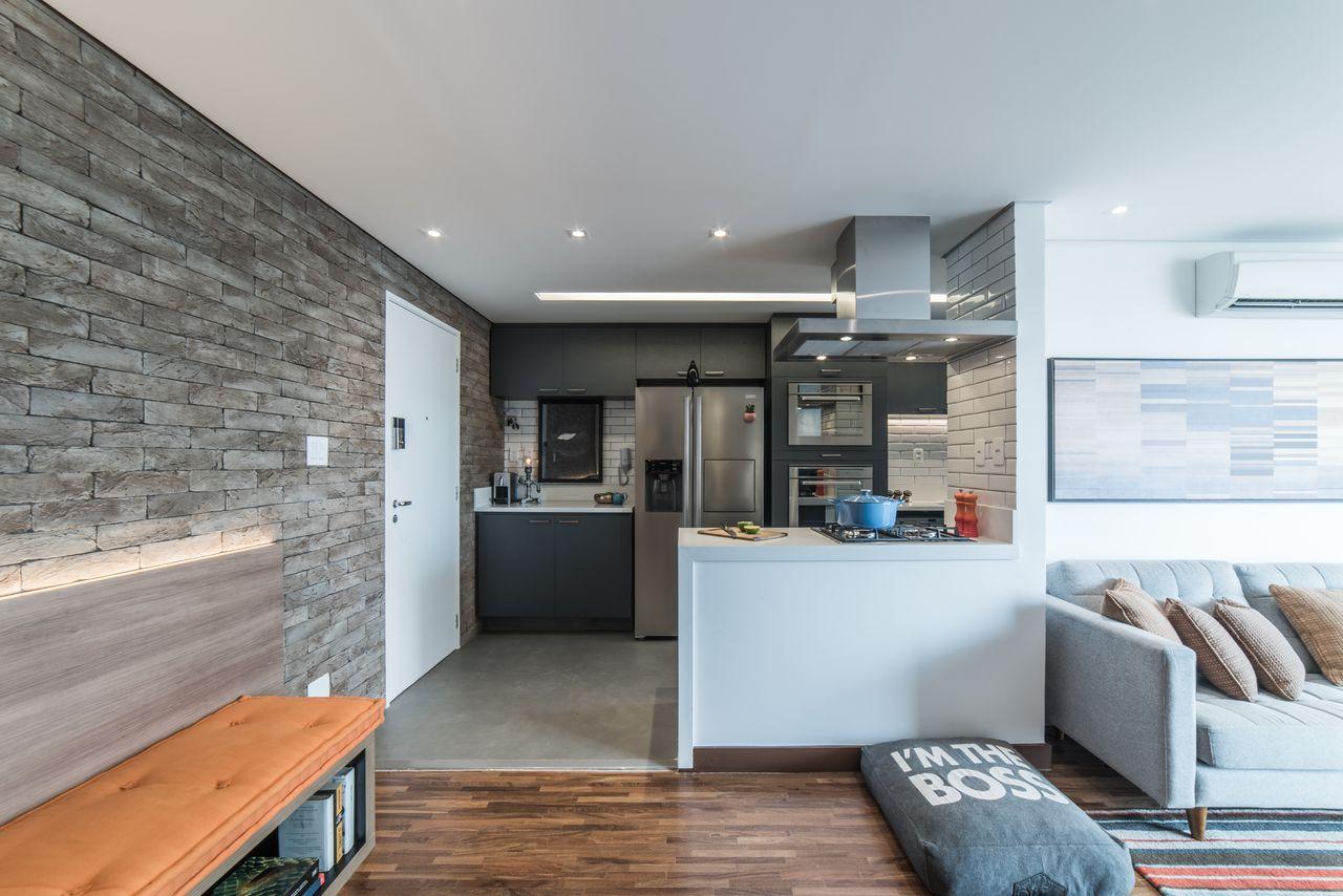 Cozinha americana com sala moderna e parede de tijolinho de pedra.