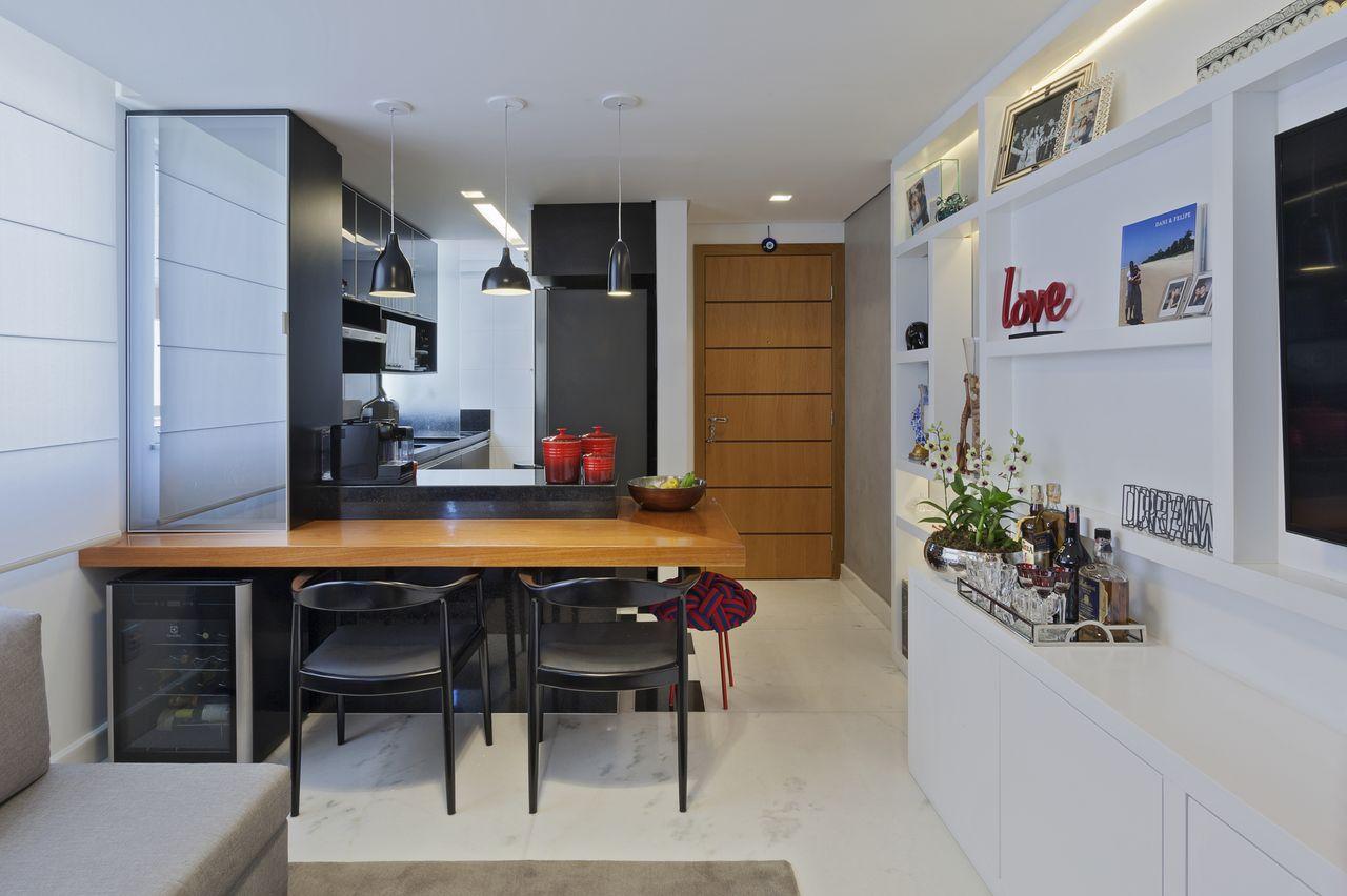 Cozinha americana com sala e armários pretos.