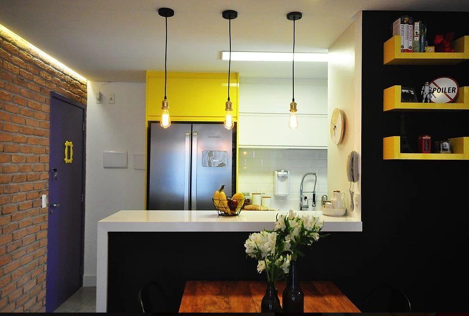 Decoração com armário amarelo e bancada branca iluminada por pendentes suspensos modernos.
