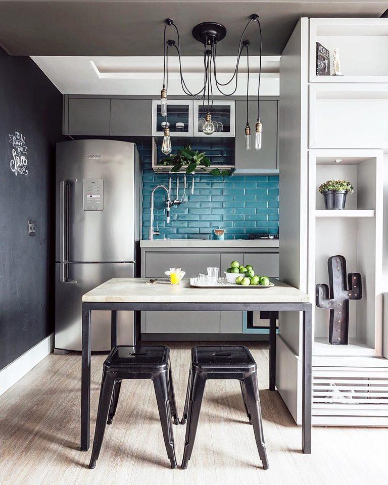 Cozinha americana moderna com azulejo azul e lustre moderno.