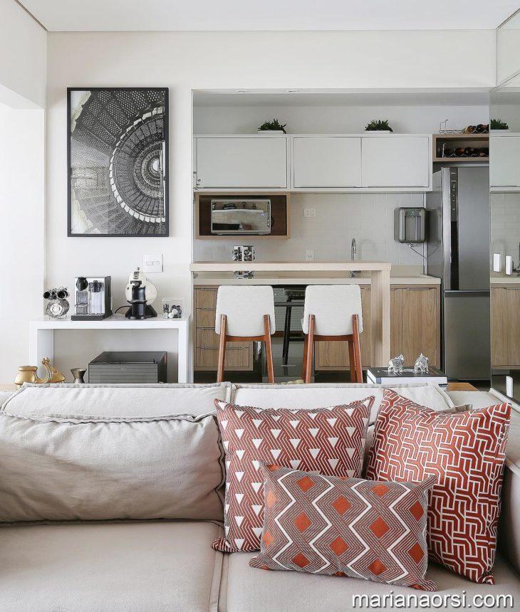 Cozinha americana simples com armários em tons neutros.