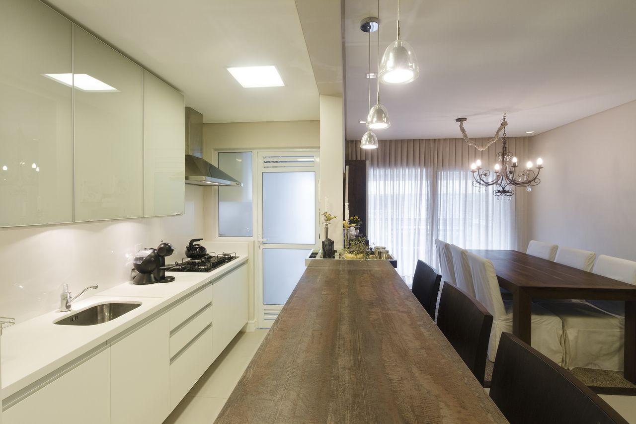 Cozinha americana com armários brancos e bancada de madeira.