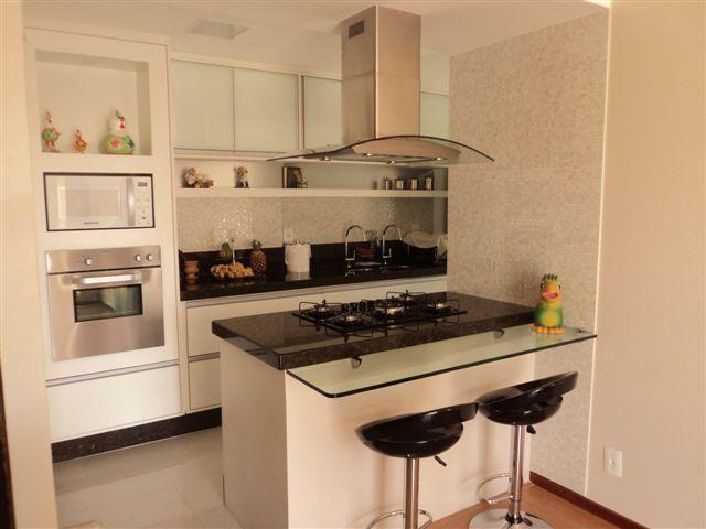 Cozinha americana simples com cooktop e bancada de vidro.