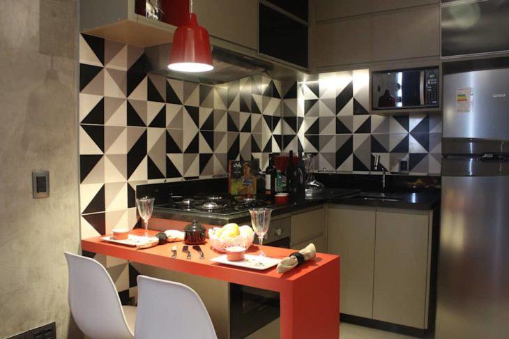 Cozinha americana moderna com bancada laranja de madeira.