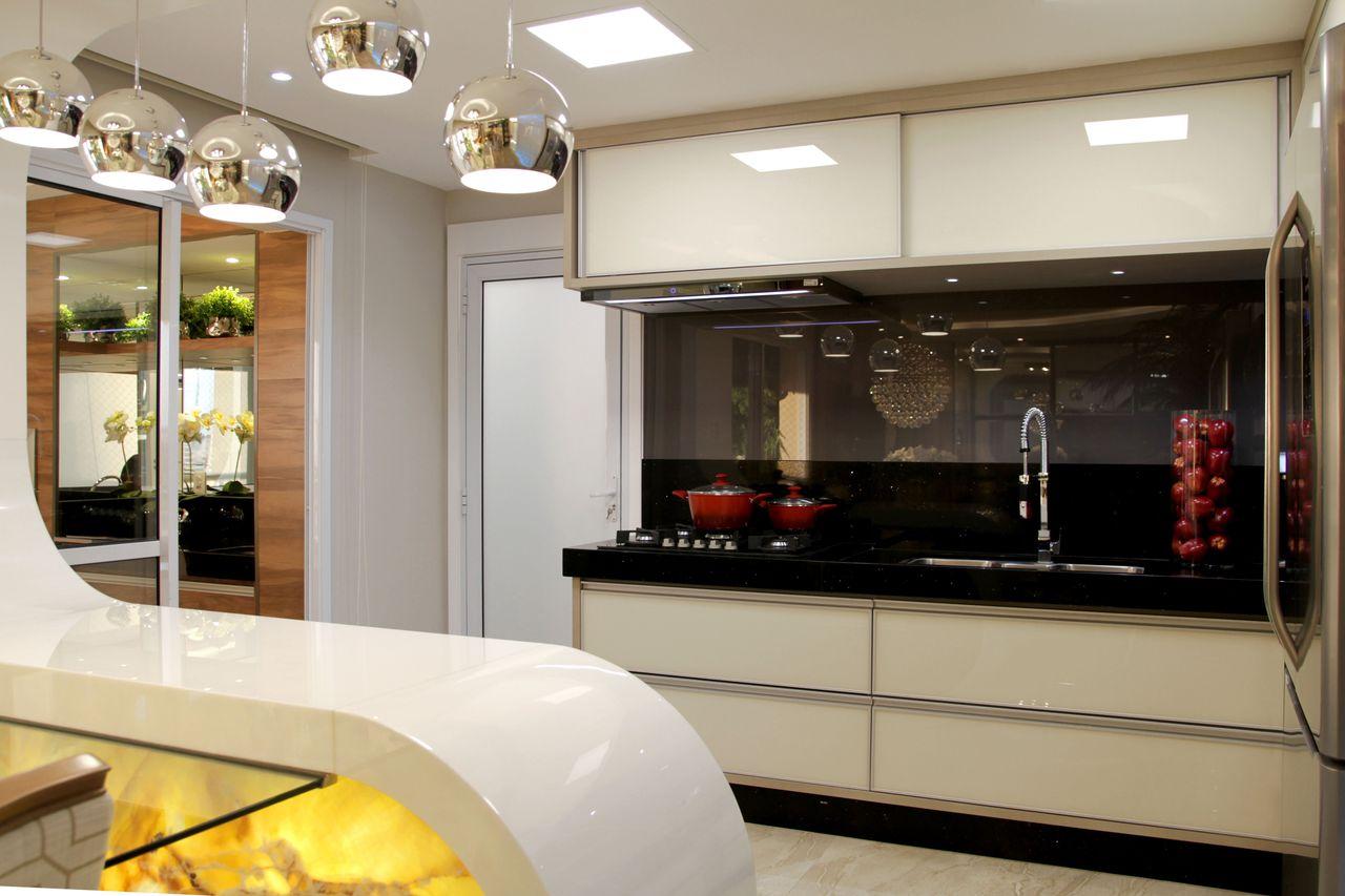 Cozinha americana moderna com armários brancos e bancada futurista.
