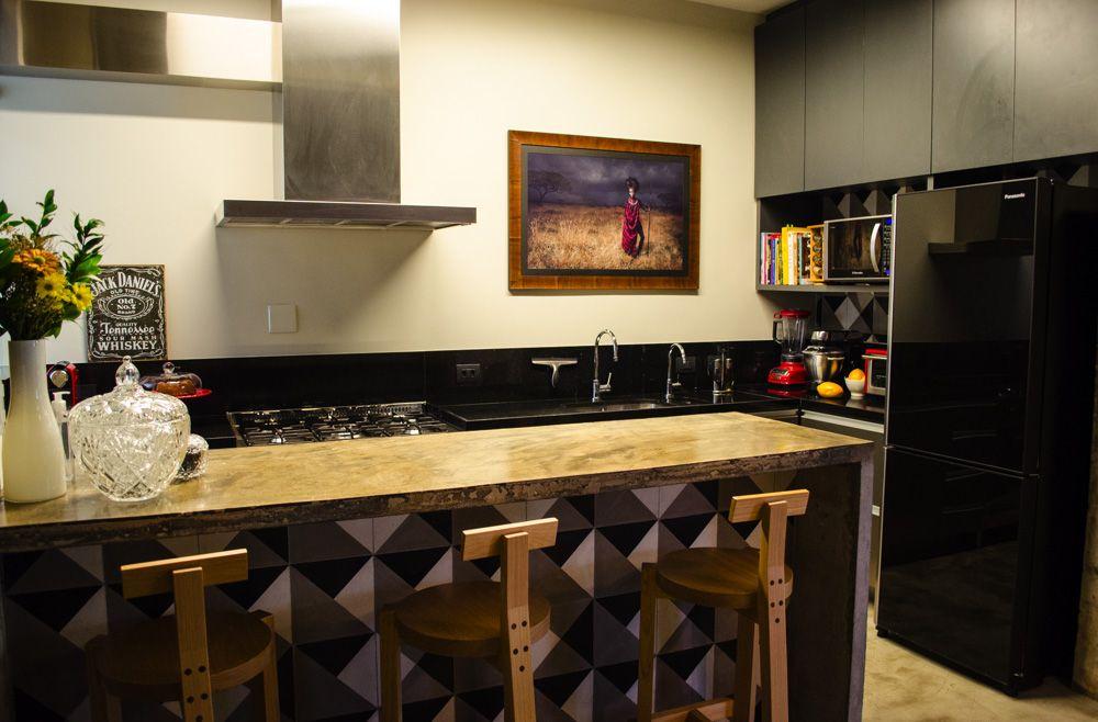 Cozinha americana moderna com bancada de concreto e geladeira preta.