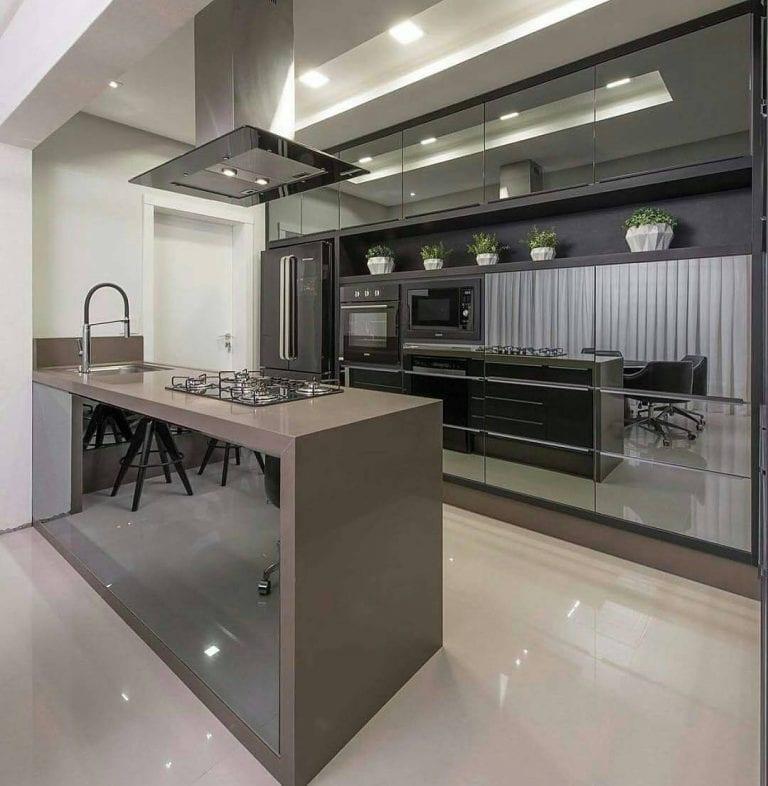 Cozinha americana luxuosa com armários espelhados.