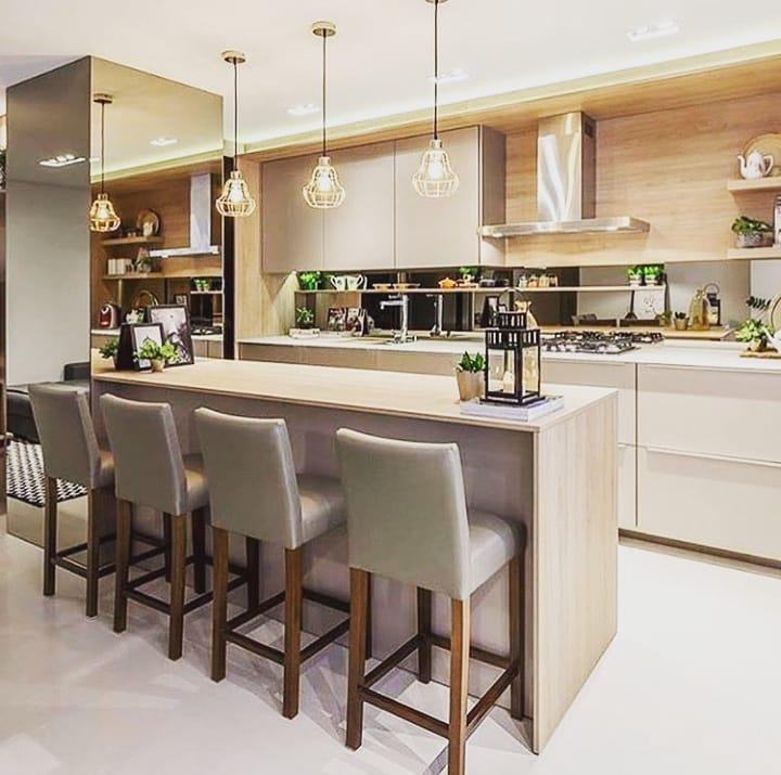 Cozinha planejada luxuosa com armários em tons neutros e espelhos.