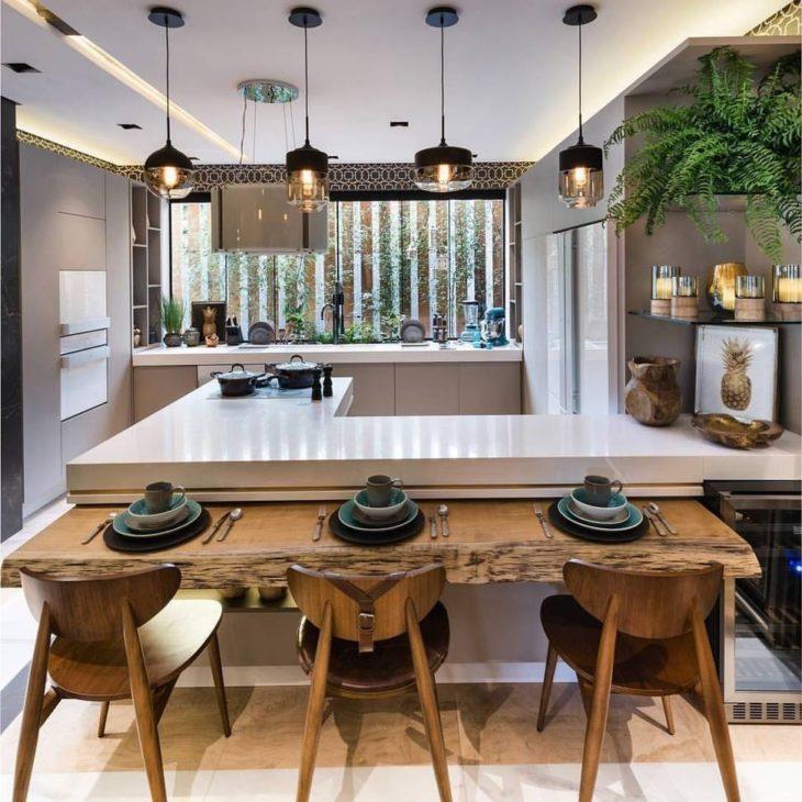 Cozinha americana luxuosa com pendentes suspensos, cooktop e bancada rústica de madeira.