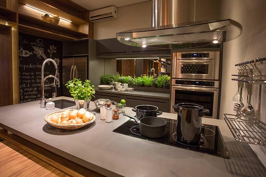 Decoração luxuosa e moderna com geladeira de inox e bancada com cooktop.