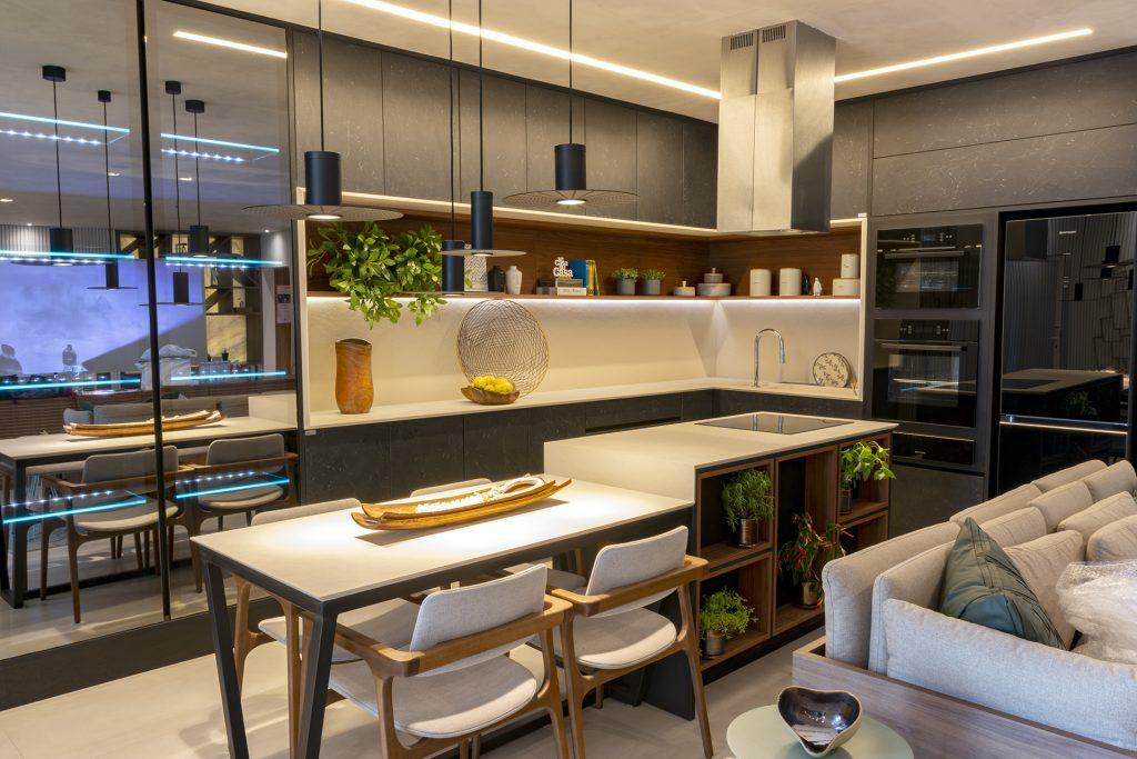 Cozinha americana de luxo com armários pretos, pendentes suspensos modernos e cooktop.