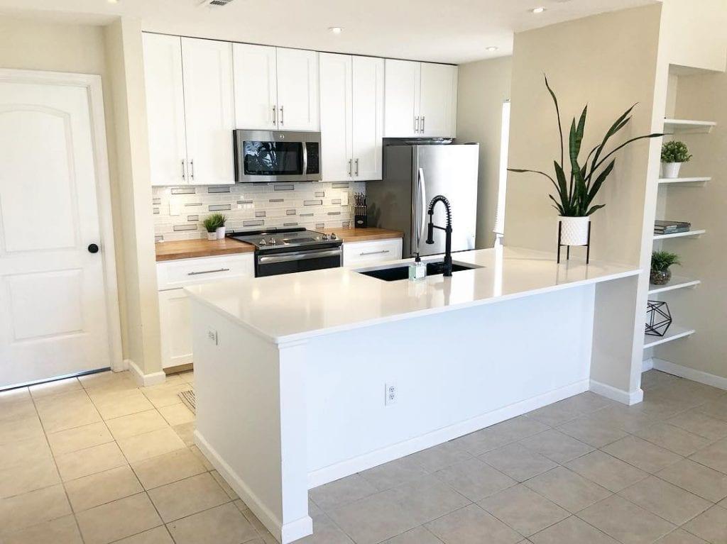 Cozinha planejada simples com armário branco.